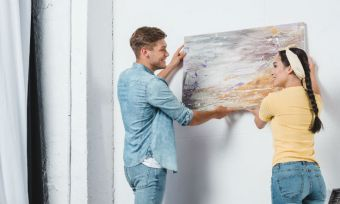 Couple hangs a painting