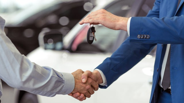 Car dealer shaking hands: Sell a car with finance owing