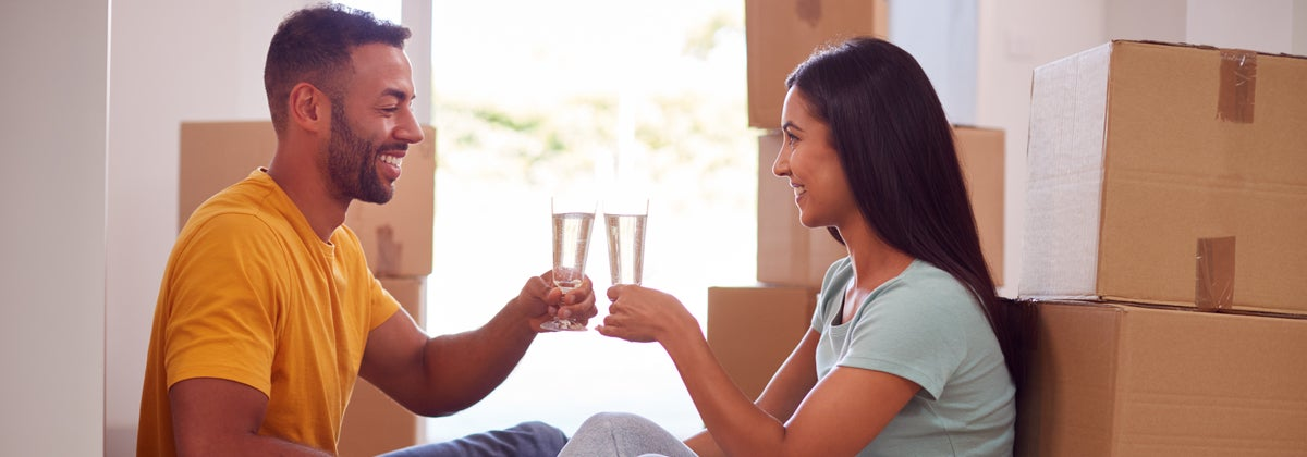 Young couple toasting moving into their first home with champagne