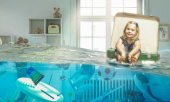 Picture of little girl floating in suitcase in her flooded bedroom