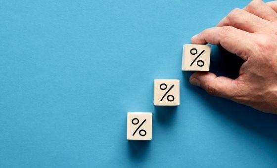 hand placing three rising wooden blocks marked with percentage symbols